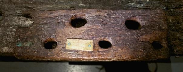 """Klossen som er tolka som """"sliding deadman"""" ligg på benkeplata. Den har gjennomgåande hol omlag slik som føtene har. I enden har den eit spor som kan passe til lista som er festa på undersida benkeplata. Foto: Roald Renmælmo"""