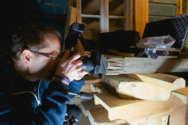 Dendroøkologen Andreas Kirchhefer tar makrofoto av endeveden på høvelbenken for å datere planken. Foto: Roald Renmælmo