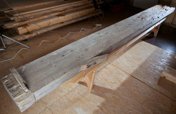 """Høvelbenken som er funnen under stabburet på Helberg. Benken består av ein 6 alen (3,8 m) lang planke som er 15"""" brei og 4"""" tjukk. På flasken har den høvelstopp i form av ei bjørkelist som er 1 ⅛"""" (28 mm) høg. På sida har den ei bordklype som er spikra på. Eg har ikkje funne noko understell som høyrer til benken men det er spor etter spikar på undersida."""
