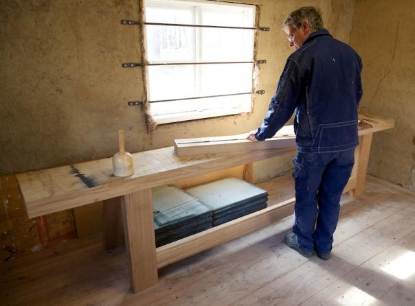 Tomas arbeider med tverrtrea på benken som står på føtene sine. Tverrtrea vart tilpassa og spikra fast med smidde spikar. Foto: Roald Renmælmo