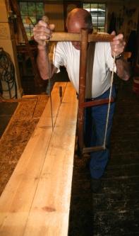 Sjur står på sida av bordet og sagar. Legg merke til kniven som er sett fast i sagskåret for å motverke at saga knip. Foto: Roald Renmælmo
