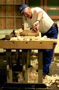 For å kontrollere høvlinga brukar han kanten av høvelen som rettholt. Det gjer han medan bordet er fastspent i benken. Foto: Roald Renmælmo
