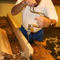 Emnet er spent fast med baktanga mellom benkehakane når han borrar for slissane i langrabatane (sideramtrestykka). Foto: Roald Renmælmo