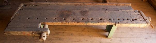 Høvelbenk i samlinga på Lundenes bygdetun. Benken er kring 185 cm lang og 60 cm brei over framtanga. Benken er bygd av ein planke som er 24 cm brei og 45 mm tjukk og går i heile lengda. Den har baktang av hjulmakartype og høvelbenkskuff som er omlag 20 cm brei. Foto: Roald Renmælmo