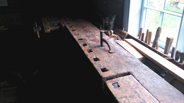 Høvelbenken med ronghake på Romsdalsmuseet i Molde. Høvelbenken har registreringsnummer R 6061 og ronghaken har R 6096. Dei kjem frå NIls Klauset i Molde. Dei er utstilt i ein snikkarverkstad i eit hus som kjem frå Tresfjord men høyrer ikkje til i det huset. Foto: Øyvind Vestad, Romsdalsmuseet