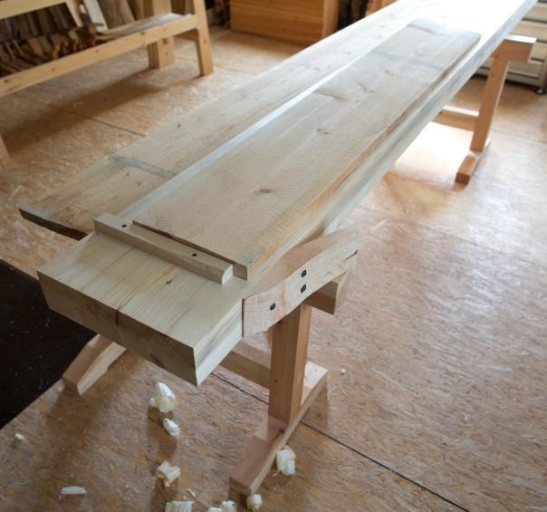 Benkeplata på dei lause bukkane. Eg har lagt eit bord mot høvelstoppen. Ved litt forsiktig prøvehøvling verka benken å vere stødig og ha rett høgd. Med grovstilt okshøvel så flyttar benkeplata på seg. Ei form for festing blir truleg nødvendig. Den originale benken frå Helberg har ein del spor etter spikar som kan ha vore slik festing. Bukkane er så breie at det er plass til å legge frå seg bord som skal høvlast bakom benkeplata. Foto: Roald Renmælmo