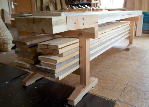 Dei lause bukkane eg laga som understell til benken fungerer fint for lagring av material. Her har eg fått plass til 16 stk golvbord. Vekta gjer at bukkane vert mykje stødigare. Det kjennast godt når ein høvlar. Foto: Roald Renmælmo