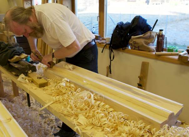 Jarle brukar ein stor staffhøvel med sponutkast i sida for å høvle siste finpussen på staffen på mønekjølen. Foto: Roald Renmælmo
