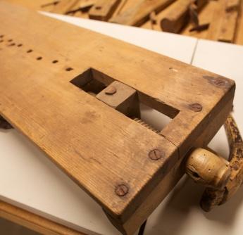 Høvelbenk frå samlinga til Romsdalsmuseet i Molde. Benkehaken i baktanga står fast. Den liknar på nokre større tilsvarande på vanlege høvelbenkar men er veldig liten. Foto: Roald Renmælmo