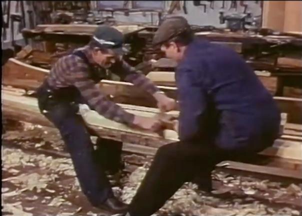 """Skjermdump frå filmen """"Från vrång til sjösättning"""" som viser båtbyggarfamilien Holmström i Klungsten i Sverige. Her har dei lagt ein grov planke på to bukkar og brukar det som benk for mykje av arbeidet dei gjer på båten."""