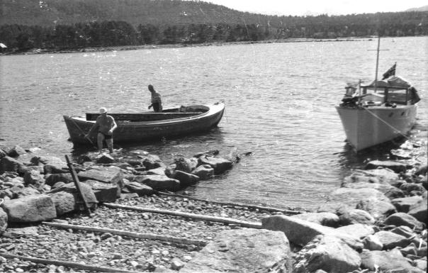 Fiskerimuseet på innsamlingstur til Hovdenakken. Fiskerimuseet ved Erling Lyngvær og Heramb Aamot (badebukse) henter gjenstander fra Thomas Skjeviks båtbyggeri, Hovdenakken, til Fiskerimuseet på Hjertøya. 1968. Høvelbenken er lagt om bord i motorsnekka.