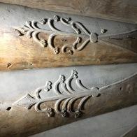 Det er to etasjar med tømmer i loftet. Særleg 2. høgda har tømmer som er fint forma og dekorert. Her er dekoren ved sida av hovuddøra i 2. høgda. Mønsteret står ut frå resten av tømmerstokken. Foto: Roald Renmælmo